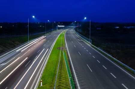 ON THE ROAD AT NIGHT - Car traffic on a modern expressway