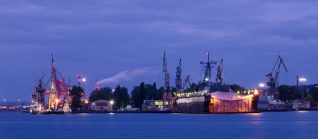 EVENING HARBOR LIFE - Illuminated waterfront and repair dock of the Navy shipyard in Gdynia