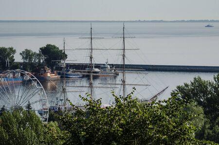 SEAPORT - Sailing ship and small ships behind trees