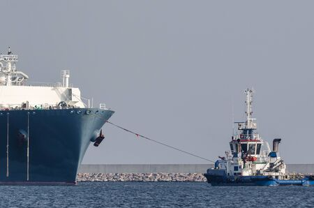 TUG BOAT AND LNG TANKER - A large ship in a seaport