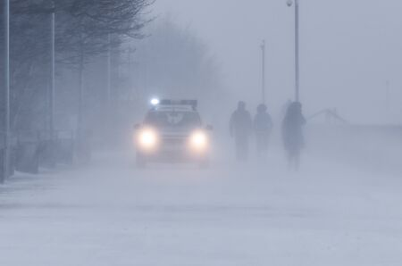 BLIZZARD ON THE BOULEVARD - People and police patrol in winter weather 版權商用圖片