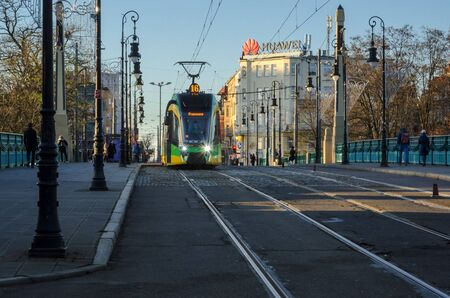 POZNAN  POLAND - 2019: Modern tram at bus stop in city center on the Theater Bridge