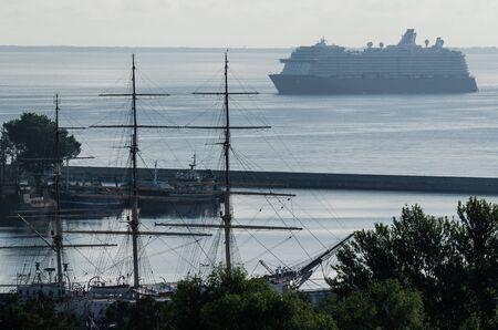 SEA COAST - Sailing vessel in port and luxury cruise ship on the horizon Stok Fotoğraf