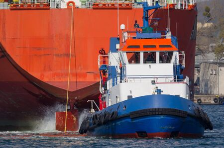 MARITIME TRANSPORT - A Tugboat and freighter maneuver in port Stok Fotoğraf