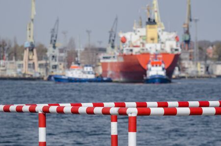 SEAPORT - Safety barriers on the port quay and a red ship with tugs in background Stok Fotoğraf