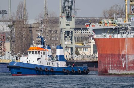 MARITIME TRANSPORT - A Tugboat and freighter maneuver in seaport Stok Fotoğraf