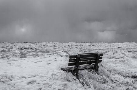 BENCH AND HURRICANE ON THE SEA COAST - Foamed sea waves during a storm