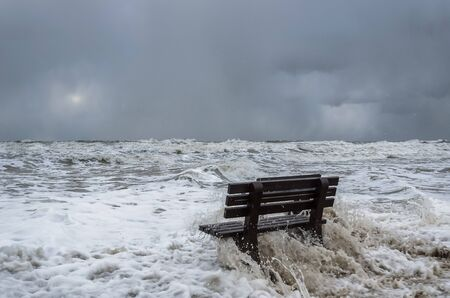 BENCH AND HURRICANE ON THE SEA COAST - Foamed sea waves during a storm Stock Photo