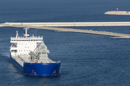 MARITIME TRANSPORT - The ship sails through the port channel to the transhipment terminal