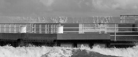 STORM AT SEA - Sea waves crash into the walking pier on coast