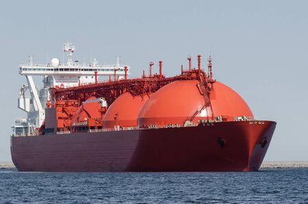 GNL TANKER - Le beau navire rouge se dirige vers le quai de déchargement du terminal gazier