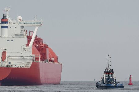 LNG TANKER - The beautiful red ship flows to the gas terminal unloading quay