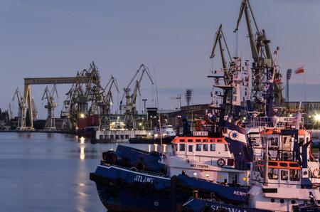 SZCZECIN, WEST POMERANIAN / POLAND - 2020: Tugs tucked to the port quays against the background of shipyard docks Sajtókép