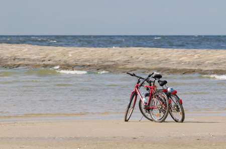 SWINOUJSCIE, WEST POMERANIAN / POLAND - 2020: Two bikes on the sea beach at the breakwaters of the seaport
