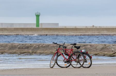 ON THE SEA COAST - Two bikes on the sea beach at the breakwaters of the seaport Фото со стока