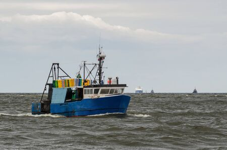 FISHING - A fishing boat at sea and LNG tanker in the background