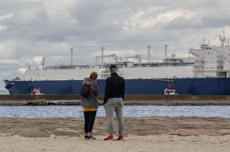 SWINOUJSCIE, WEST POMERANIAN / POLAND - 2020: The LNG tanker maneuvers for mooring at gas port terminal