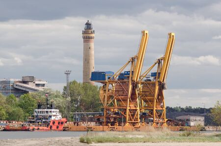 SEAPORT - A red ship moored at the quay, transshipment terminal and lighthouse