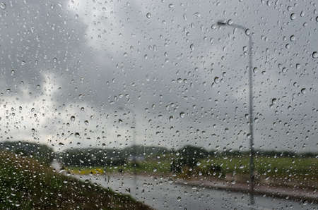 RAIN DROPS ON THE GLASS - Heavy rain over the road