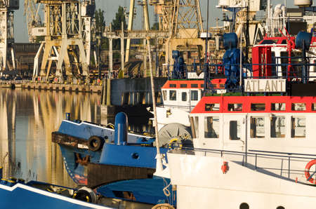 SZCZECIN, WEST POMERANIAN / POLAND - 2020: A tugboat at wharf with shipyard in the background