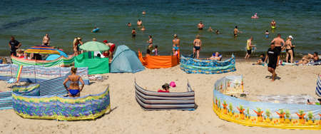 SARBINOWO, WEST POMERANIAN / POLAND - 2020: Holiday tourists relax on the sunny sea beach 新聞圖片
