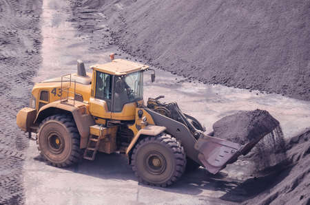 SWINOUJSCIE, WEST POMERANIAN / POLAND - 2020: The wheel loader works in a fossil mineral storage yard 新聞圖片