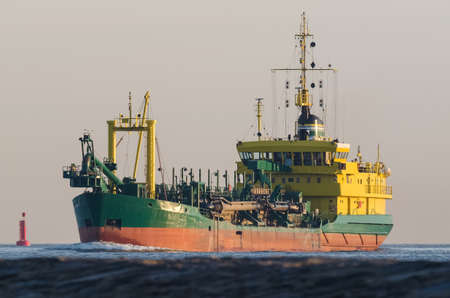 HOPPER DREDGER - A specialized vessel travels on a waterway at sea
