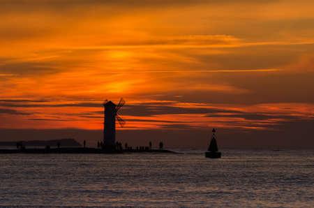 NAVIGATION SIGN ON THE BREAKWATER - Sunset on the seashore in Swinoujscie Standard-Bild