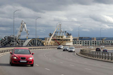 CAR TRAFFIC ON CITY ROAD - Landscape of a port city with a ship in the background