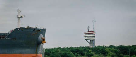 BULK CARRIER AND TRAFFIC CONTROL TOWER AT SEA - Freighter entering a seaport