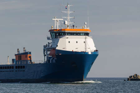MERCHANT VESSEL - A ship with a load is traveling on a waterway
