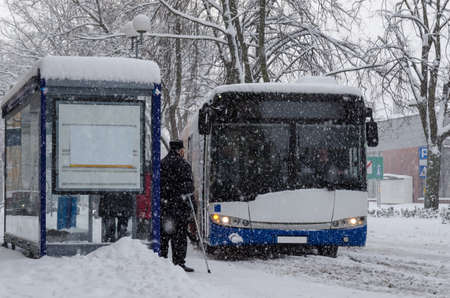 WINTER ATTACK - People and city bus on the snow covered stop and street