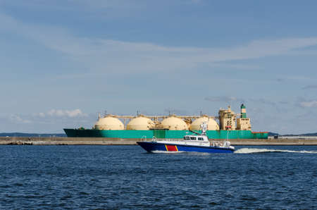 BORDER GUARDS BOAT AND LNG TANKER - Officers secure ship and the gas terminal