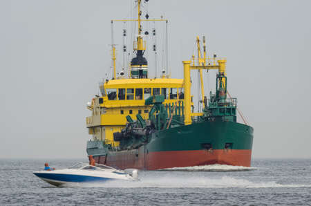 HOPPER DREDGER - A ship sailing on the sea and a fast motorboat Foto de archivo