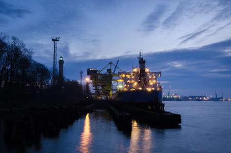 MARITIME TRANSPORT - A merchant vessel at a transshipment quay in a seaport 免版税图像