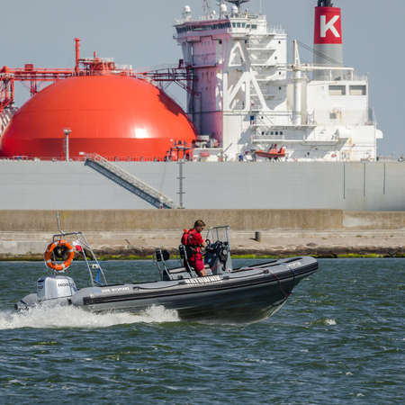 SWINOUJSCIE, WEST POMERANIAN / POLAND - 2020: Lifeguard on a fast boat and LNG tanker in the background 新闻类图片