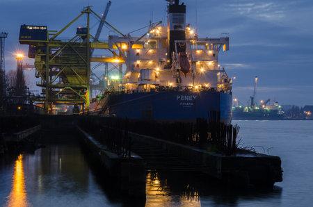 SWINOUJSCIE, WEST POMERANIAN - POLAND - 2020: A merchant vessel at a transshipment quay in a seaport 新闻类图片