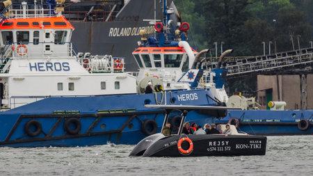 SWINOUJSCIE, WEST POMERANIAN - POLAND - 2020: Tourists travel along the port canal on a small solar boat