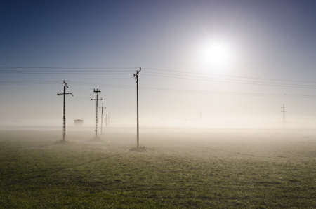POWER ENGINEERING - High voltage power line in a misty meadow