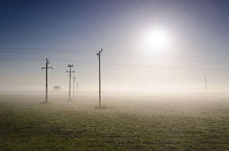 POWER ENGINEERING - High voltage power line in a misty meadow Standard-Bild