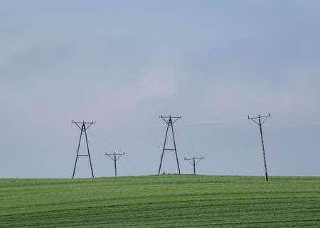 POWER ENGINEERING - High voltage power line in a green field Standard-Bild
