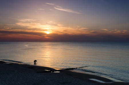 SUNSET OVER THE SEASHORE - Sun, beach and man in the water