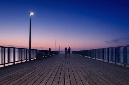 PIER ON THE SEA COAST - Womens walk at a quiet sunset