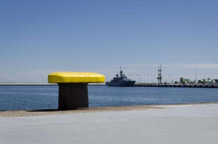 YELLOW BITT - Seaport wharf with warship in the background 版權商用圖片