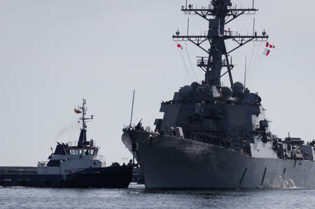 WARSHIP - US Navy guided missile destroyer maneuvers in the port assisted by a tugboat