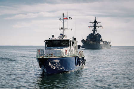 GDYNIA - POLAND - 2021: Maritime office boat and American warship in the port