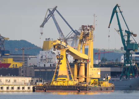 CRANE SHIP - A specialized yellow machine moored at the quay of seaport 版權商用圖片