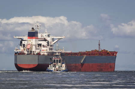BULK CARRIER - The ship sails from port to sea secured by tug 版權商用圖片