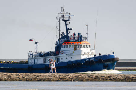SWINOUJSCIE, WEST POMERANIAN - POLAND - 2020: Holidaymakers walk on the breakwater and tugboat goes to the port