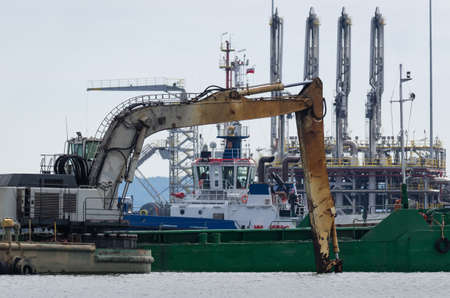 CONSTRUCTION WORK AT LNG TERMINAL IN SEAPORT - Excavator on a floating work platform